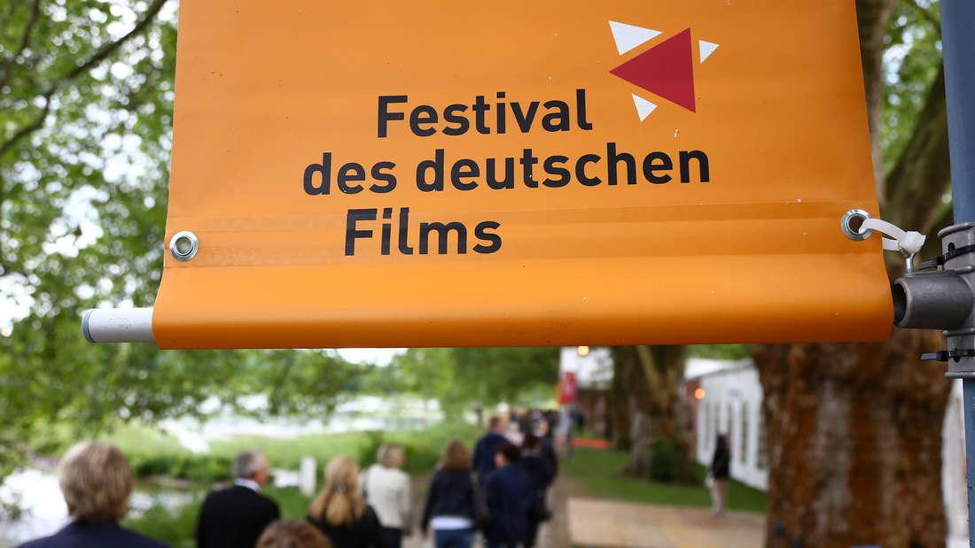 Besucher der Eröffnungsveranstaltung des Festivals des deutschen Films gehen über die Parkinsel. (Archivfoto 2018)