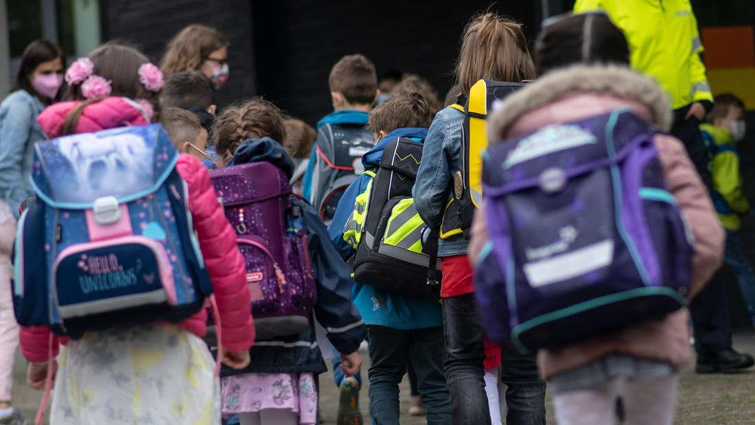 Kinder mit Schultaschen.
