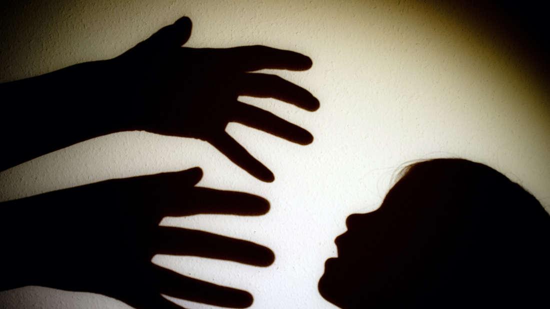 Schatten-Hände greifen nach dem Schatten-Kopf eines Kindes.