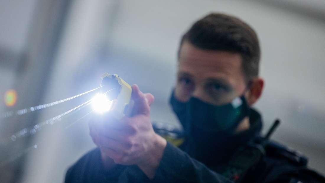 Ein Polizeibeamter demonstriert einen Schuss mit einem Taser