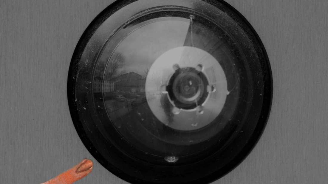 Eine Alienhand greift nach der Linse einer Überwachungskamera